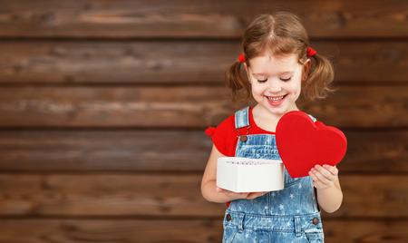 Gelukkig lachend kind meisje met cadeau Valentijnsdag, houten achtergrond