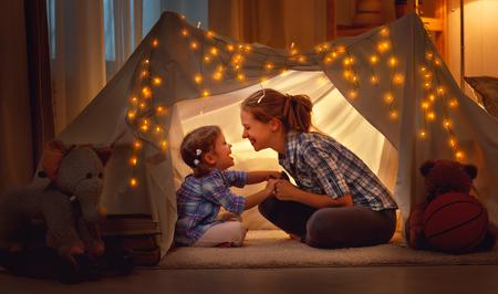 幸せな家族母と娘の自宅でテントの中で演奏