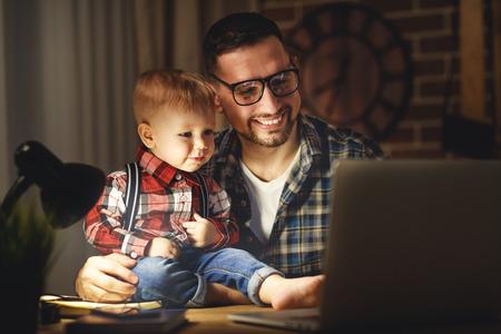 父と息子 babywork 自宅で暗闇の中でコンピューター 写真素材