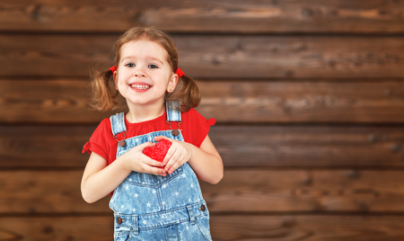 happy laughing child girl with heart Valentines Day, wooden background