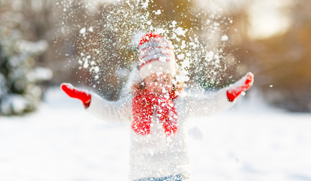 happy child girl throws up snow on a winter walk