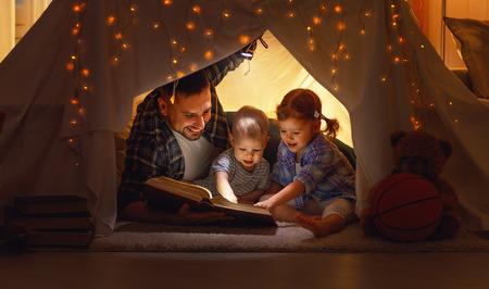 gelukkig gezin vader en kinderen het lezen van een boek met een zaklamp in een tent thuis