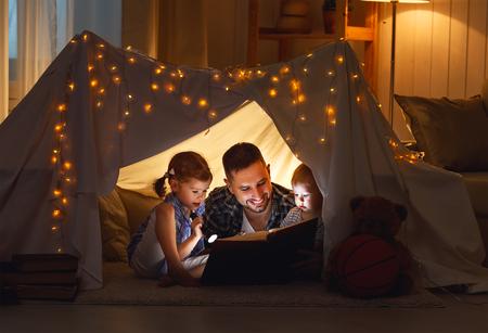 Felice padre di famiglia e bambini a leggere un libro con una torcia in una tenda a casa Archivio Fotografico - 70185451