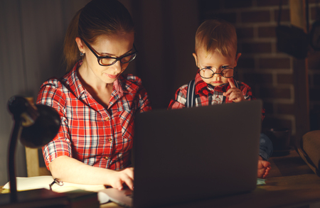 インターネット経由でコンピューターの後ろに赤ちゃんを自宅で働いて女の母 写真素材