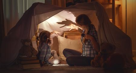 Madre hija asusta niño cuenta historias de miedo, juega en el teatro de sombras Foto de archivo - 70185338