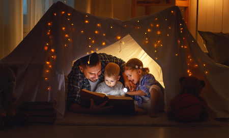 happy family father and children reading a book with a flashlight in a tent at home  Stock Photo
