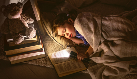 child girl sleeping in a tent with a book and a flashlight home  Banco de Imagens