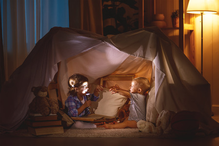 frighten: children boy and girl playing and frighten each other with flashlight in  tent at night
