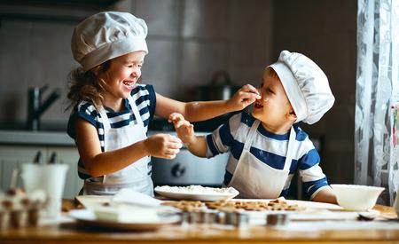 キッチンでクッキーを焼いて、幸せな家族の面白い子供は生地を準備しています。