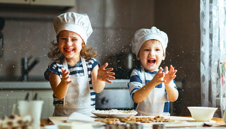 baking cake: happy family  funny kids are preparing the dough, bake cookies in the kitchen