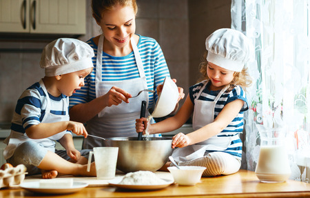 baking cake: happy family in the kitchen. mother and  children preparing the dough, bake cookies