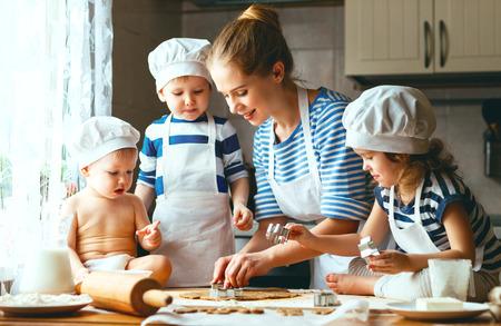 flour: familia feliz en la cocina. madre y los niños preparan la masa, hornear galletas