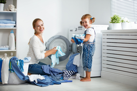 family mother and child girl little helper in laundry room near washing machine and dirty clothes  Stok Fotoğraf