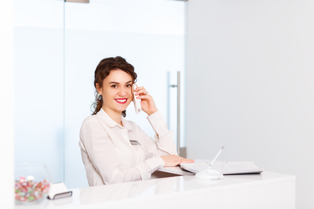 friendly young woman behind the reception desk administrator Banque d'images
