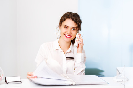 friendly young woman behind the reception desk administrator Banco de Imagens