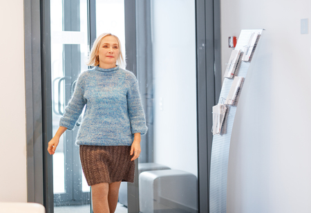 enters: happy elderly woman enters the office door, or the hospital  Stock Photo