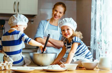 台所での幸せな家族。母と生地、クッキーを準備する子どもたち