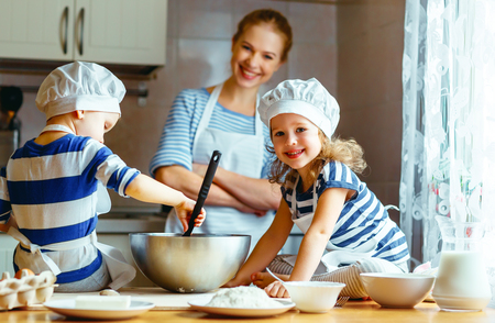 happy family in the kitchen. mother and  children preparing the dough, bake cookies Zdjęcie Seryjne - 72448640