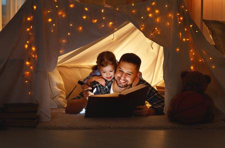 felice padre di famiglia e figlia bambino che legge un libro con una torcia in una tenda a casa