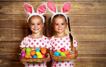 부활절 축복 받으세요! 나무 배경에 계란 토끼처럼 옷을 입고 귀여운 쌍둥이 소녀 자매