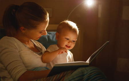 mother reads to baby the book before going to sleep in bed Stock Photo