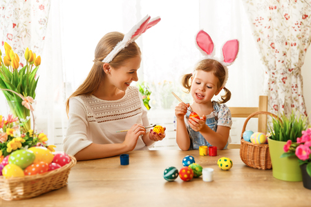 painting: Happy easter! family mother and child daughter paint eggs for holiday Easter at home