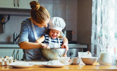 부엌에서 행복 한 가족입니다. 엄마와 아기 딸 반죽을 준비, 빵 쿠키 스톡 콘텐츠