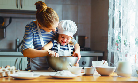 happy family in the kitchen. mother and  child daughter preparing the dough, bake cookies