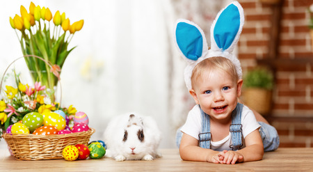 happy easter! happy funny baby boy playing with Easter bunny Stock Photo - 73047325