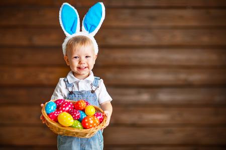Happy Baby in Osterhase Anzug mit einem Korb mit Eiern Standard-Bild - 73211996