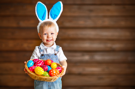 Happy baby boy in Easter bunny suit with a basket of eggs Banque d'images