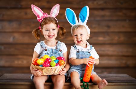 Glückliche Kinder, Jungen und Mädchen gekleidet als Osterhasen mit Korb mit Eiern auf hölzernen Hintergrund lachen