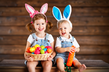 Happy kids boy and girl dressed as Easter bunnies laughing with basket of eggs on wooden background