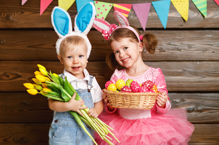 Happy kids boy and girl dressed as Easter bunnies laughing with basket of eggs and flowers on wooden background Banco de Imagens