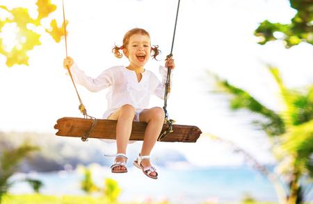 Gelukkig kind meisje lachen en swingende op een schommel op het strand in de buurt van de oceaan in de zomer Stockfoto