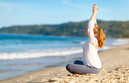 meditates: woman practices yoga and meditates in the lotus position on the beach