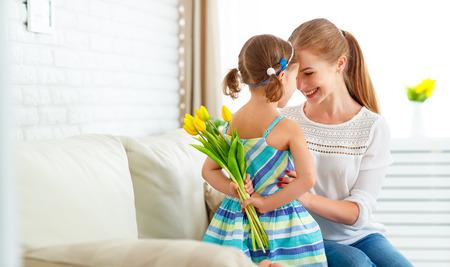 Schönen Muttertag! Kinder Tochter gratuliert Mütter und gibt ihr eine Postkarte und Blumen Tulpen Standard-Bild - 73883267