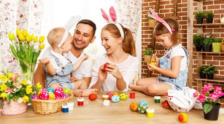 幸せなイースター!ホストファミリーのお母さんが、父と子供たちの楽しいペイントし、の休日のための卵を飾る