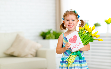 Happy mother's day! Child girl with postcard and flowers tulips for mom Stock Photo