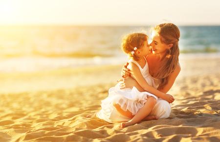 gelukkig gezin op het strand. moeder knuffelen baby dochter bij zonsondergang
