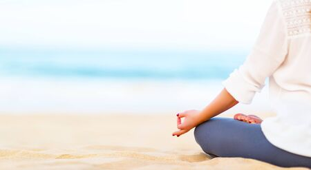 meditates: hand of woman practices yoga and meditates on the beach