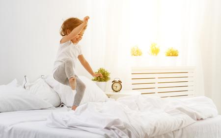 gelukkig kind meisje met plezier springt en speelt bed Stockfoto