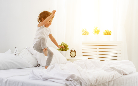 happy child girl having fun jumps and plays bed