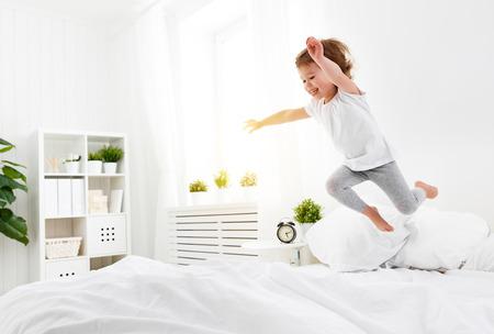Glückliches Kind Mädchen mit Spaß springt und spielt Bett Standard-Bild - 73968247
