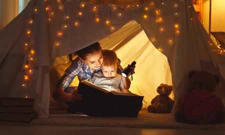 niños estudiando: lectura y juegos de la familia en la tienda de los niños. madre y el niño hija con el libro y una linterna antes de ir a la cama