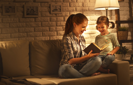 Family before going to bed mother reads to her child daughter book near a lamp in the evening 스톡 콘텐츠