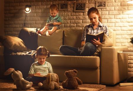 Familie voor het naar bed gaan moeder en kinderen lezen boeken en spelen 's avonds rond de lamp