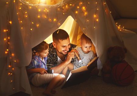 Felice padre di famiglia e bambini a leggere un libro con una torcia in una tenda a casa Archivio Fotografico - 73968292
