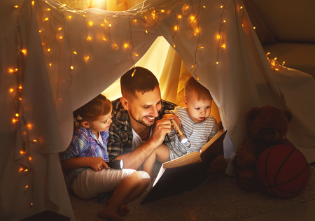 happy family father and children reading a book with a flashlight in a tent at home 版權商用圖片 - 73968292