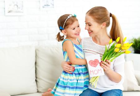 해피 어머니의 날! 어린 딸은 엄마를 축하하고 그녀에게 엽서와 꽃 튤립을 제공합니다